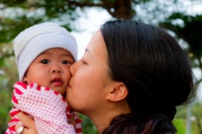 mom kissing infant