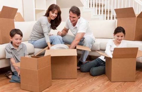 parents and kids filling up moving boxes