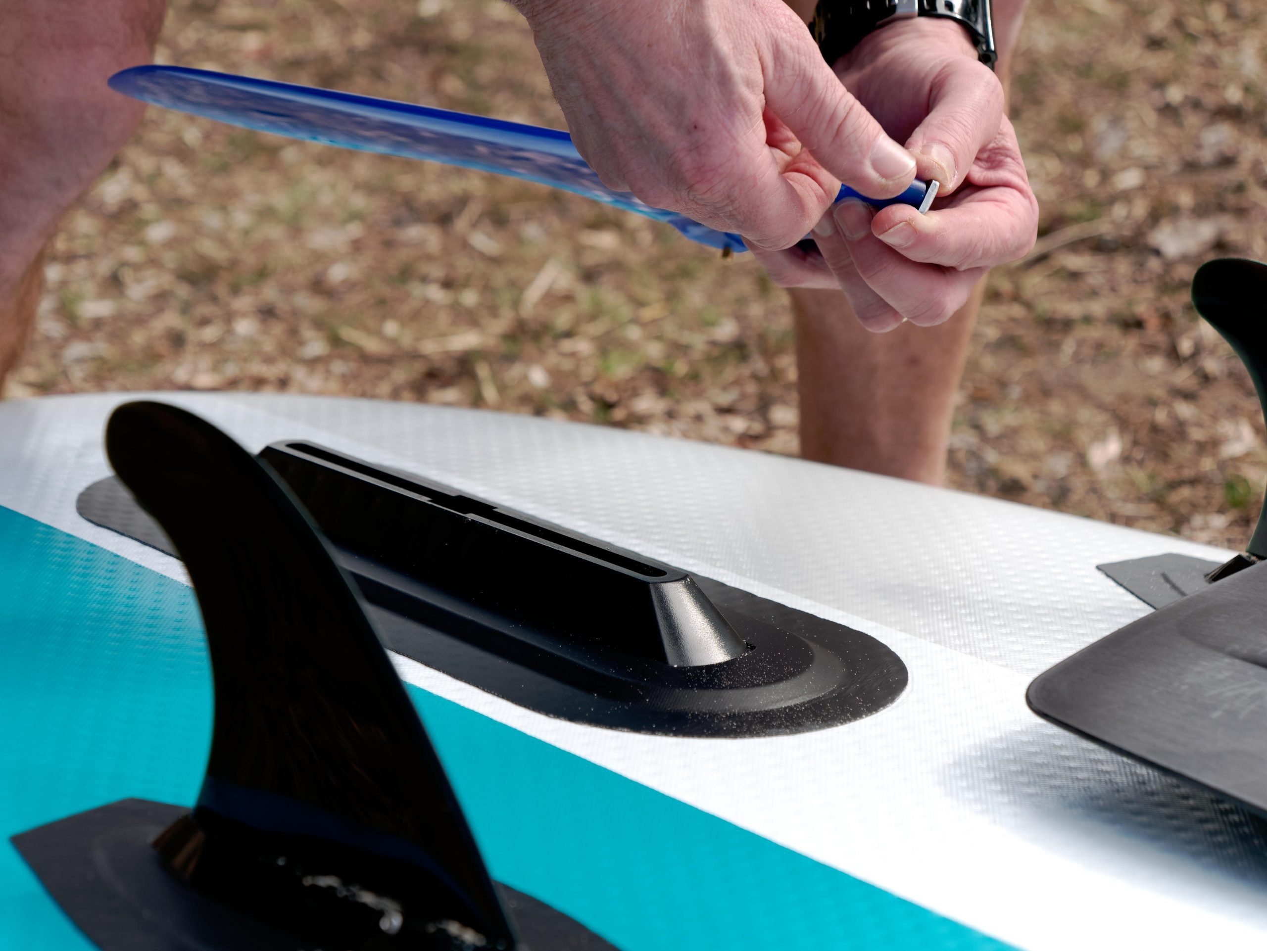 Putting a fin on and inflatable paddle board