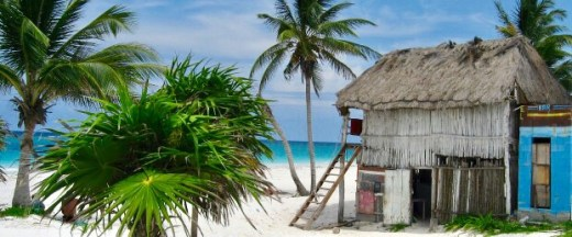 a beach cabana near the sea with palm trees in Tulum, Mexico