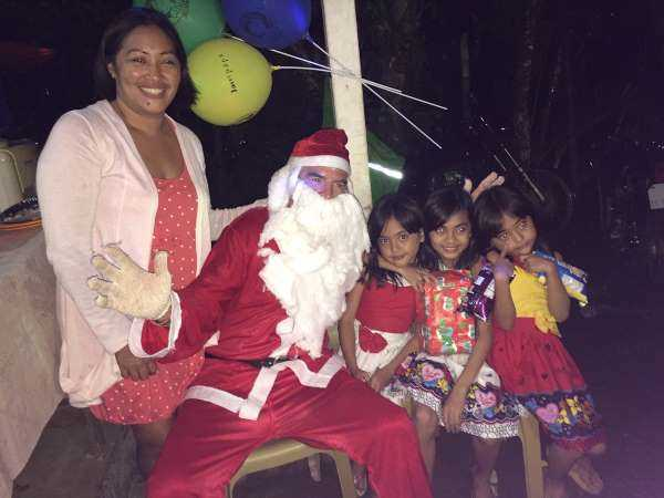 Woman and three children with Santa pose for a picture at a holiday party in the Philippines