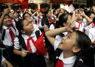School pupils cheer as they release balloons during a ceremony held  at a primary school in Hanoi to mark the new school year. (Photo: AAP)