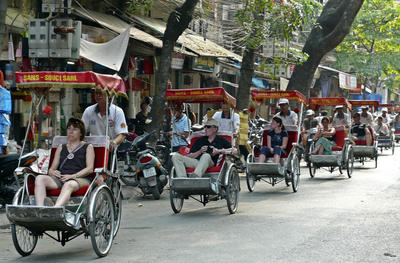 Tourists ride cyclos in the Old Quarter neighborhood in Hanoi, Vietnam. Vietnam and PNG have yet to fully harness the opportunities of a vibrant services sector. (Photo: AAP)