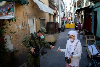 A soldier wearing a protective mask checks a woman's quarantine pass as the city undergoes a stricter lockdown to contain the coronavirus disease (COVID-19) spread, in Pasay City, Philippines, 22 April 2020 (Photo: Reuters/Eloisa Lopez).