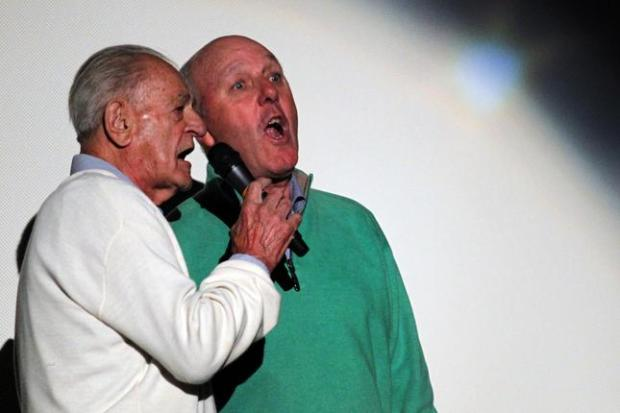 """Anthony """"Lil"""" Arnerich, left, founder of Alameda Recreation & Park Department's legendary T-shirt baseball league, and Bill Sonneman, former Encinal High School principal, sing """"Take Me Out To The Ball Park"""" during the """"First Pitch Benefit Party"""" at the Alameda Theatre and Cineplex in Alameda on March 20, 2014. The fundraising event celebrated the return of the Alameda recreation & Park Department's legendary T-shirt baseball league. (Ray Chavez/Staff archives)"""