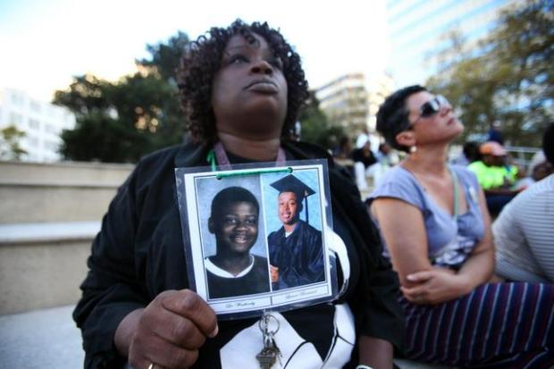 Dinyal New, holds photos of her two sons Lee Weathersby III, 13, and Lamar Broussard, 19, during a vigil for homicide victims of last year and this year at Frank Ogawa Plaza in Oakland, Calif., on Thursday, Sept. 25, 2014. Broussard was killed three weeks after his younger brother Weathersby was gunned down on New Year's eve of 2014. The vigil was organized by Khadafy Foundation for Non-Violence, a grief support group for parents who have lost a child due to violence. (Ray Chavez/Bay Area News Group)