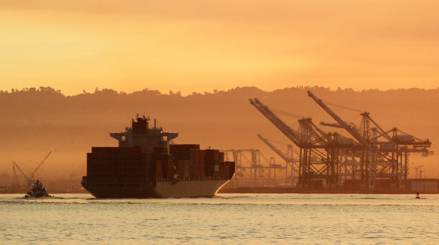 A container ship makes its way through the bay waters toward the Port of Oakland as the sun breaks through the morning fog on Tuesday, July 26, 2016 in Oakland, Calif. (Laura A. Oda/Bay Area News Group)