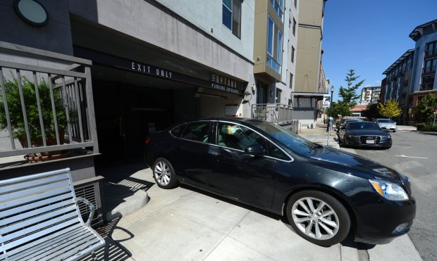A car exits the underground parking of one of the Uptown Apartment buildings in downtown Oakland, Calif., on Tuesday, Sept. 20, 2016. The Oakland City Council is expected to vote to approve major reductions to its off-street parking requirements. (Dan Honda/Bay Area News Group)