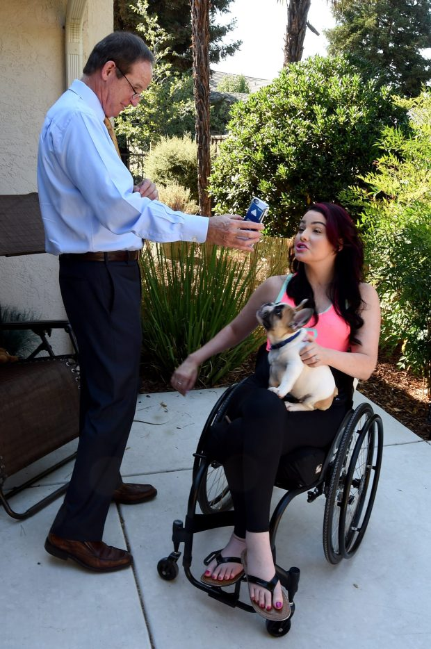 Attorney Timothy Tietjen shares a cell phone photo of his dog with Rebecca Forkey, of Walnut Creek, who holds her dog Pork Chop on her lap at her home in Walnut Creek, Calif., on Thursday, Sept. 8, 2016. Forkey was injured in a car accident when a distracted driver trying to do a good deed, pursued an impaired driver causing the accident which left her a paraplegic. She received a $24 million settlement of a lawsuit for debilitating injuries she suffered in a highway collision in May 2013 on I-680 in Walnut Creek. (Susan Tripp Pollard/Bay Area News Group)