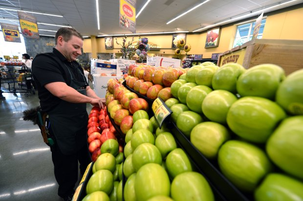 Cail Howland stocks the apple display on the first day of business at the Safeway store in The Orchards shopping center in Walnut Creek, Calif., on Wednesday, Sept. 14, 2016. (Kristopher Skinner/Bay Area News Group)