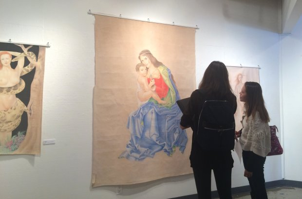 Visitors to the Diablo Valley College Art Gallery look at the works by Omid Mokri, a prison inmate who used recycled bedsheets as canvases, pulverized color pencils for paint, and his own hair attached to plastic spoons as a paintbrush.