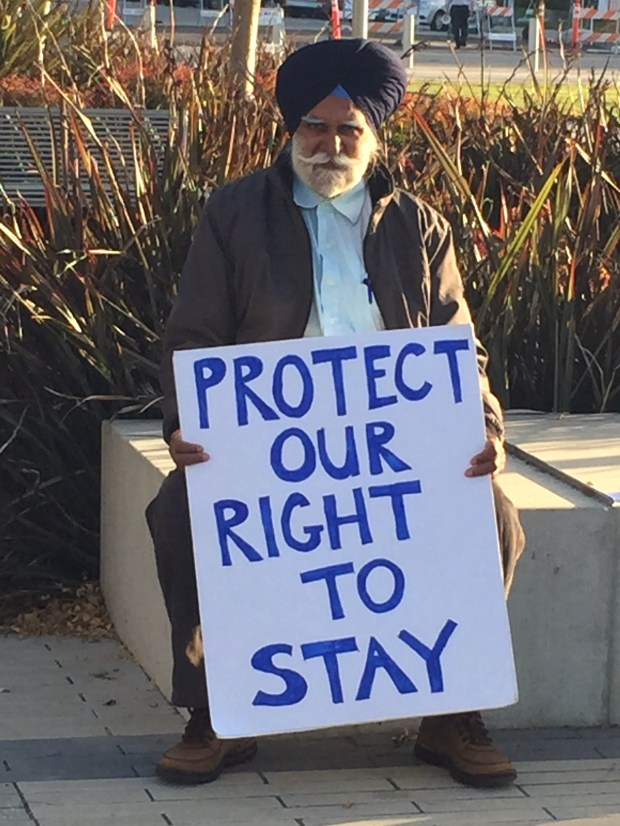 A supporter of an emergency moratorium on rents waits outside Richmond City Hall Tuesday.