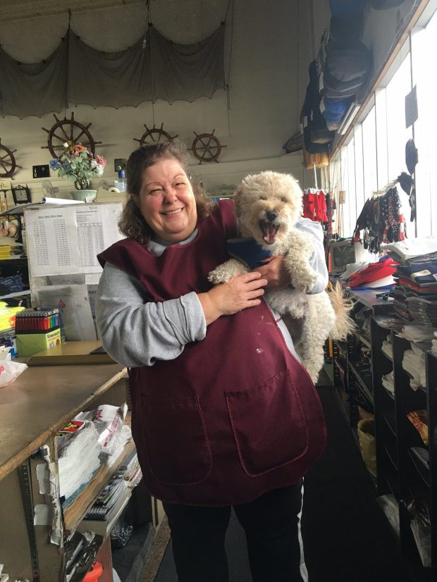 Patricia Titus starts out her day behind the counter at the Bonanza store at 3435 International Blvd. in the company of her son's pooch, Benny.