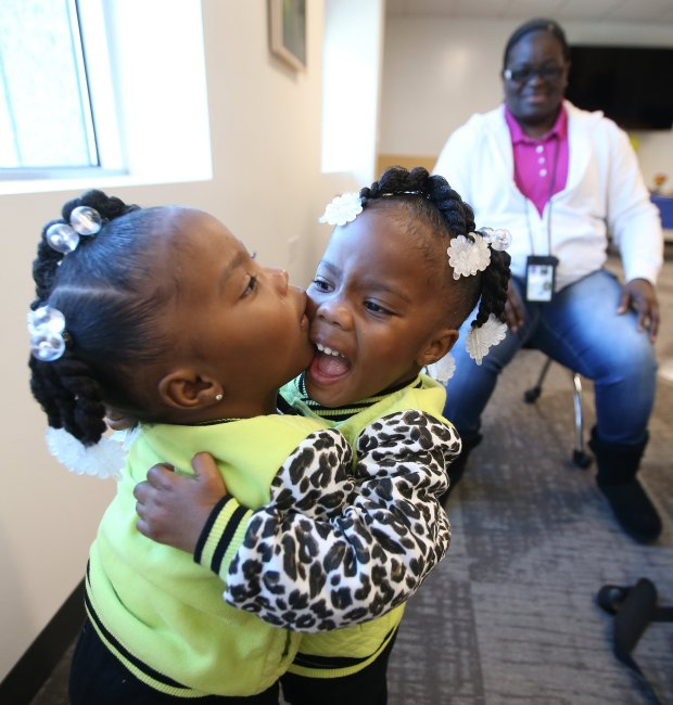 Twin sisters Hope and Faith Bowen ,2, hug during a adoption celebration event at the Alameda County Social Services Agency on Wednesday, Nov. 16, 2016, in Oakland, Calif. (Aric Crabb/Bay Area News Group)