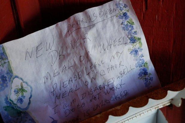 A weathered note is posted on the front door of Milton Williams' front door with instructions for the Meals on Wheels driver at his home in Oakland, Calif., on Wednesday, Nov. 16, 2016. Williams, 95, has been a recipient of the Meals on Wheels program for about ten years, allowing him to live at his home of 40 years. (Laura A. Oda/Bay Area News Group)