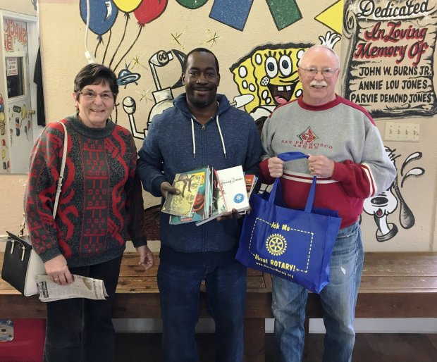 "Joan Means, left, and Richard Means, right, members of the Pleasant Hill Rotary Club, recently delivered children's and teenage books to Tyrone Burns, local hero and owner of the Oakland ""Pull Up Your Pants Barbershop."" Burns is establishing a library for neighborhood kids to encourage reading. The books were gathered by librarian and Rotarian Patrick Remer on behalf of the Pleasant Hill Library."