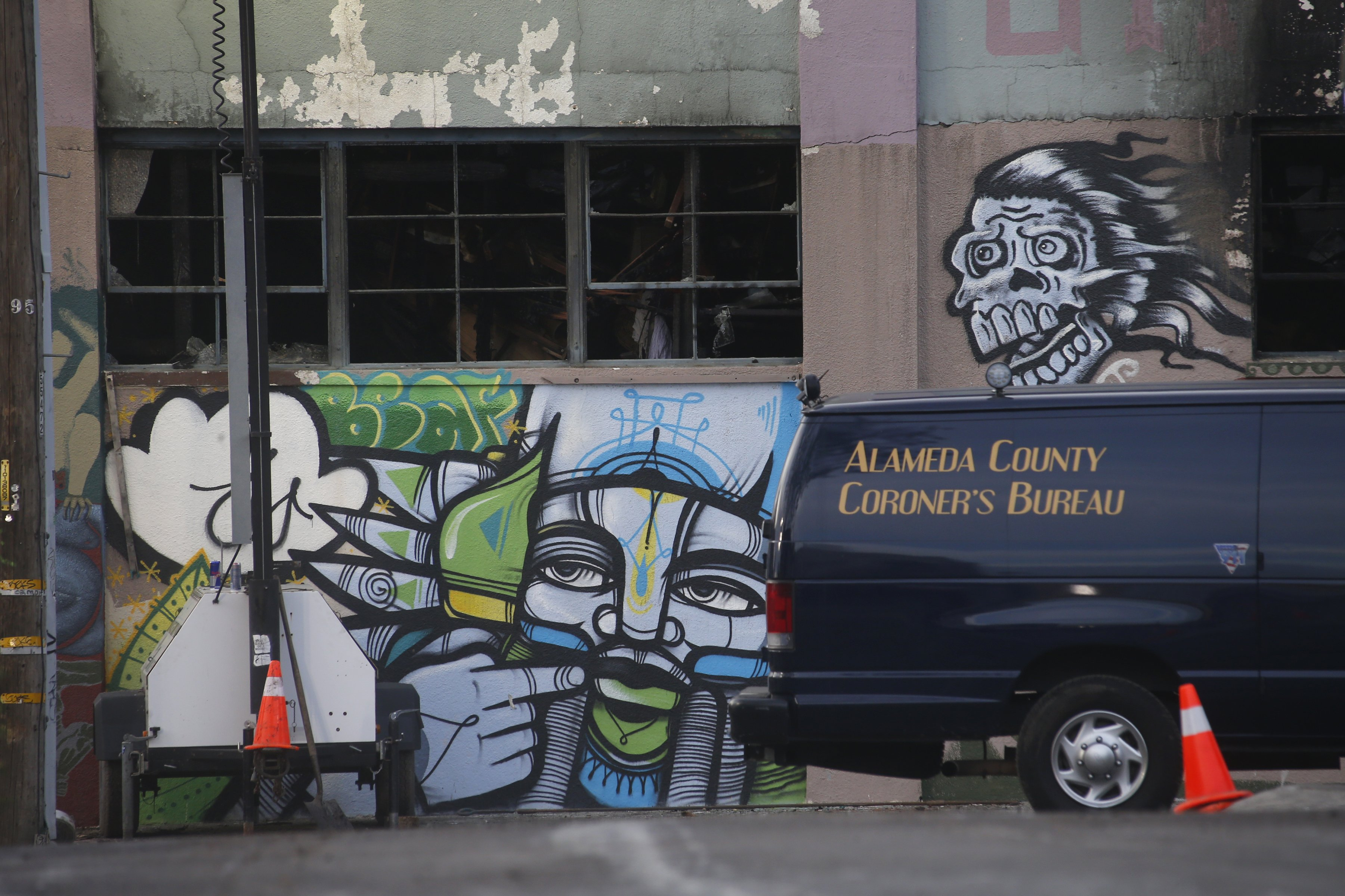 An Alameda County Coroner's van remains parked outside the fatal Ghost Ship warehouse fire in Oakland, Calif., Sunday, Dec. 4, 2016. Authorities announce late Sunday that the death toll has risen to 33. (Karl Mondon/Bay Area News Group)