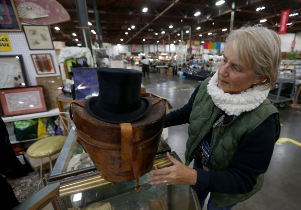 Volunteer Pam dos Remedios-Litke, of Oakland, checks out an old hat and leather hat box at the White Elephant Sale warehouse in Oakland, Calif., on Wednesday, Jan. 19, 2017. The 58th annual White Elephant Sale will be held March 4-5 at 333 Lancaster Street. A preview sale takes place Sunday, January 29, from 10 a.m. to 4 p.m. Proceeds from the sale, which has raised over $2 million dollars each of the past two years, will benefit the Oakland Museum of California. (Jane Tyska/Bay Area News Group)