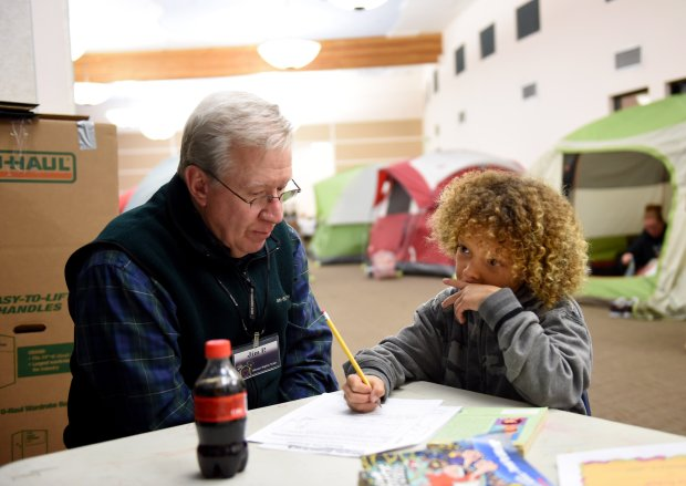 Amari Goree, 7, from the Antioch Pittsburg area, ponders his answer as he works one on one with volunteer tutor Jim Pohl, of Walnut Creek at the Warm Winter Nights shelter set up at St. John Vianney Catholic Church in Walnut Creek, Calif., on Tuesday, Jan.17, 2017. Warm Winter Nights is a rotating family shelter set up during the winter months through the Social Justice Alliance and the Interfaith Council of Contra Costa County. Amari's mom Amanda Goree works at straightening up the family tent at right the two share with three other family members. (Susan Tripp Pollard/Bay Area News Group)