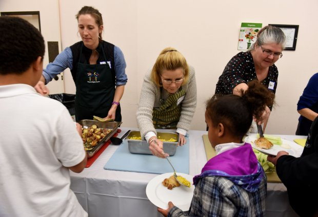 Volunteers from left, Ashlee Urmson, of Concord, Linda Locke, of Walnut Creek, and Maura Dugan Krueger, of Concord, serve dinner at the Warm Winter Nights shelter set up at St. John Vianney Catholic Church in Walnut Creek, Calif., on Tuesday, Jan.17, 2017. Warm Winter Nights is a rotating family shelter set up during the winter months through the Social Justice Alliance and the Interfaith Council of Contra Costa County. (Susan Tripp Pollard/Bay Area News Group)