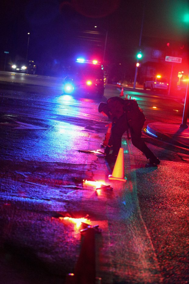 A Fremont police officer places road flares at the intersection of SutterDrive and Mowry Avenue on Sunday, Feb. 5. Fremont investigators were examining an area inside this perimeter where a man was shot and killed by a Fremont police officer on Sunday afternoon.