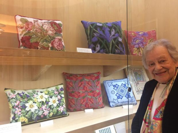 Anna Marie Levy and some of the needlepoint pillows on display at the Orinda Library gallery through the end of February.