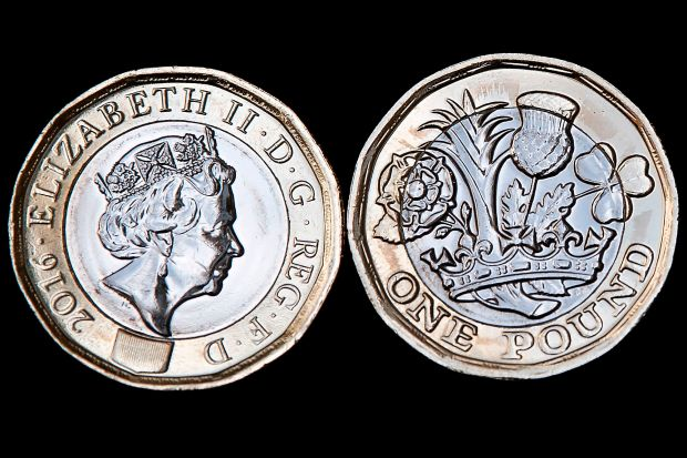 """In this posed photograph, the obverse (L), and reverse of a newly issued 12-sided £1 (one pound) coin is pictured in London on March 28, 2017.Britain's new £1 coin with the symbols of England, Scotland, Wales and Northern Ireland goes into circulation from Tuesday on the eve of the launch of a Brexit process that has put national unity in doubt. The 12-sided coin is the first change to the shape of the £1 coin since its introduction in 1983. Britain's finance ministry said the new coin would be """"the most secure of its kind in the world"""" to prevent a rise in counterfeits. The old coins will cease to be legal tender on October 15. / AFP PHOTO / Justin TALLISJUSTIN TALLIS/AFP/Getty Images"""
