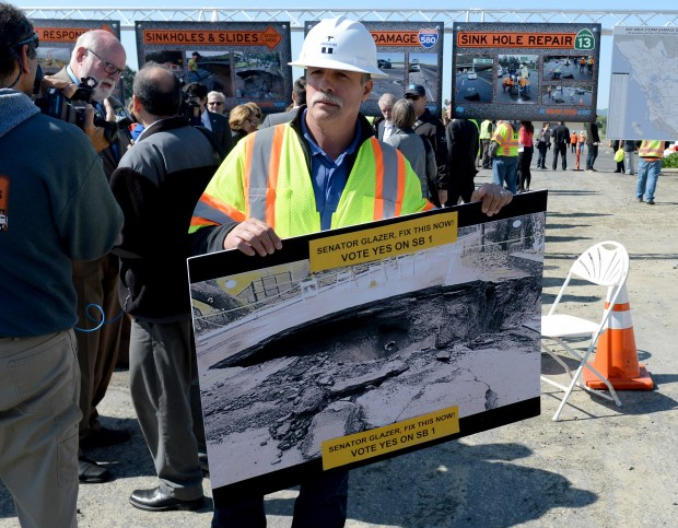 Augustin Diaz, of Fairfield, a member of the Carpenters Union carries a large photo of a sink hole with a personal message to Senator Steve Glazer as a press conference wraps up where Gov. Jerry Brown talked about a $5 billion proposal to repair California's crumbling roads and bridges by raising fuel taxes, hiking vehicle registration fees and charging electric car owners a yearly fee during a press conference in Concord, Calif., on Thursday, March 30, 2017. Brown stressed the need for the roads and bridge to be fixed now. (Susan Tripp Pollard/Bay Area News Group)