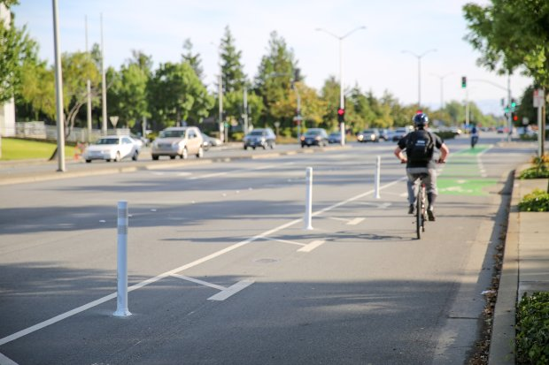 White vertical plastic cylinders with reflector tape on the top portion,known as bollards, line a portion of westbound Walnut Avenue in Fremont as a biker rides through the lane. The city is testing two different kinds of delineators to separate bike and vehicle traffic. (Photo by Joseph Geha/The Argus)