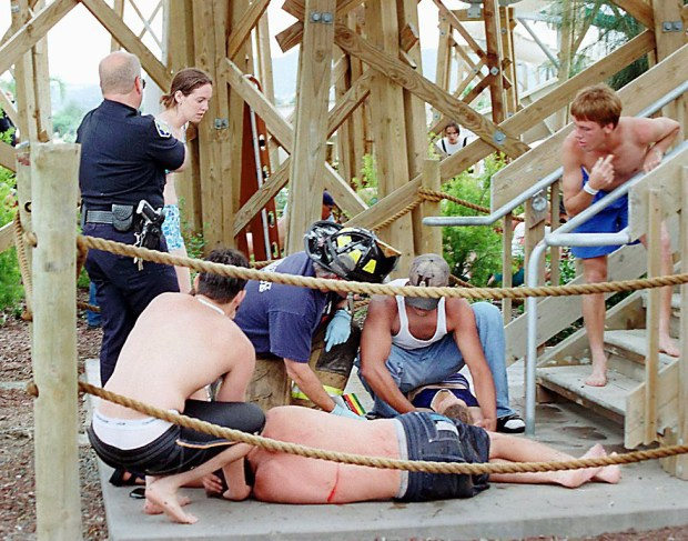 A Contra Costa, Calif., firefighter attends to two youths injured when a water slide collapsed Monday afternoon June 2, 1997 at Waterworld USA in Concord, Calif. Thirty-two students were injured and one killed in the collapse caused when a group of students tried to go down the slide together. (AP Photo/Contra Costa Times, Jeff Eide)