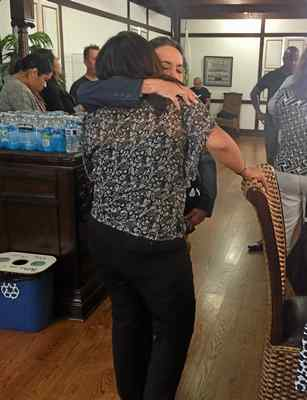 Isabel Reyes, with her back to the camera, gets a hug from Carmen Slack, a supporter of the Eric Reyes Foundation and Robby Poblete Foundation, at Wednesday's organization meeting for the Aug. 26 Solano County Gun Buyback at the Solano County Fairgrounds. (RICH FREEDMAN — TIMES-HERALD)