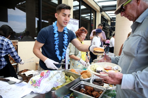 Weiland Fong, left, nephew of Farmer Joe's owners Joe and Diane Tam, serves food to longtime customer Phil Caskey during the market's 11th anniversary in the Dimond district in Oakland on June 24.(Ray Chavez/Bay Area News Group)
