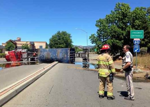 A tractor-trailer hauling food grade sunflower oil overturned Monday morning onto the Davis Street on and off ramps to Interstate 80. The driver of the truck was taken to the hospital and may have had a medical emergency while driving, according to the California Highway Patrol. (Jessica Rogness — The Reporter)