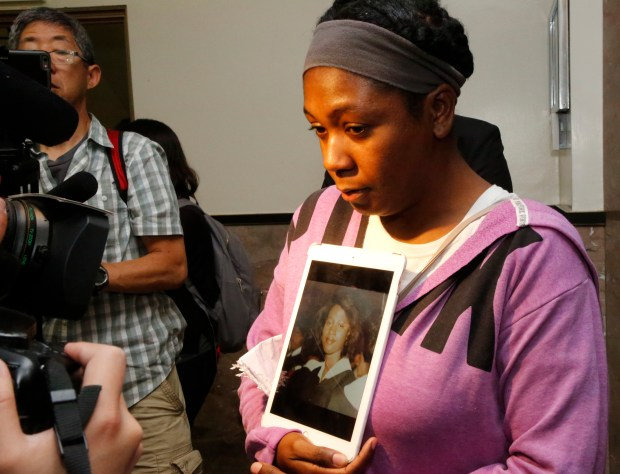 Cammella Seymour holds a photo of her mother, Judith Seymour, as she speaks to the media outside the courtroom at the Rene C. Davidson Superior Courthouse in Oakland, Calif., on Friday, July 14, 2017. Judith Seymour was one of seven victims of the Oikos University shootings by One Goh. Goh was sentenced to seven consecutive life terms and will spend the rest of his life in prison. (Laura A. Oda/Bay Area News Group)