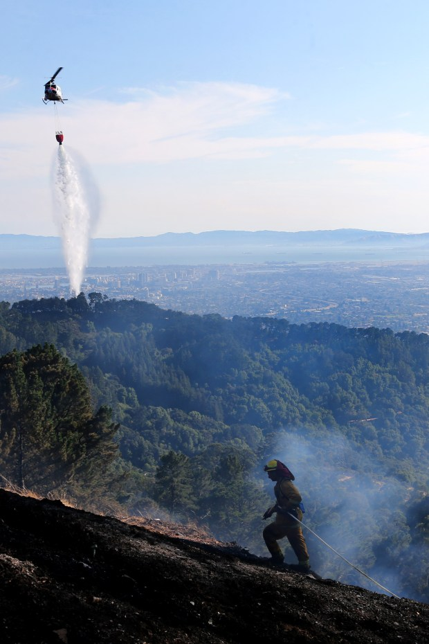 A Cal Fire helicopter drops water as firefighters battle hotspots during a brush fire along Grizzly Peak Boulevard in the Oakland-Berkeley hills in Berkeley, Calif., on Wednesday, Aug. 2, 2017. (Ray Chavez/Bay Area News Group)
