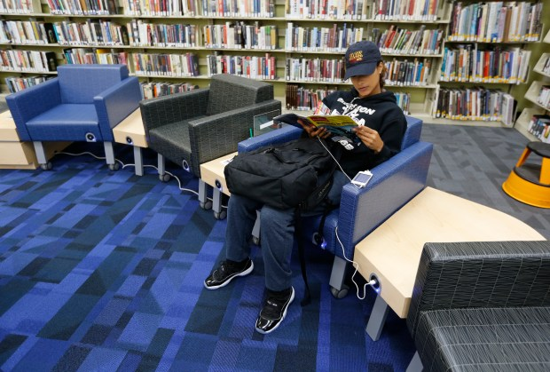 Alexis Lua from Oakland charges her phone as she looks at a magazine in the chairs that have built-in USB chargers in them at the newly refurbished Oakland Public Library, Dimond branch. (Laura A. Oda/Bay Area News Group)