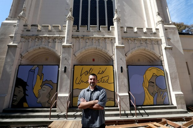 """Artist Kevin Proctor, of El Cerrito, is photographed with a mural he recently completed at Trinity United Methodist Church on Bancroft Avenue in Berkeley Calif., on Tuesday, Sept. 19, 2017. The piece displays the message """"Love is Undefeated"""" in response to the recent political divide and hate crimes in the country. (Jane Tyska/Bay Area News Group)"""