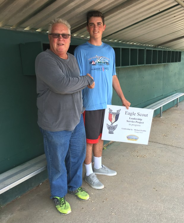 Alameda Little League President Ron Matthews congratulates Eagle Scout candidate Michael Proffitt on his Eagle Scout project to construct wooden helmet racks for four dugouts. (Courtesy of Joanne Broadbent)