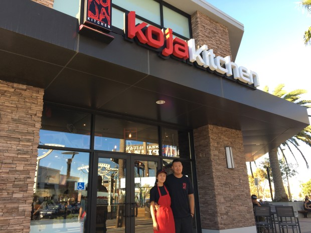 Wife-and-husband Carien and Will Kwok stand outside the popular Asian fusion Koja Kitchen in Alameda Landing, which opened Oct. 27. The restaurant specializes in rice bun burgers with Korean barbecue-style meat and Korean and Japanese rice bowls. (Sarah Tan/For Bay Area News Group)