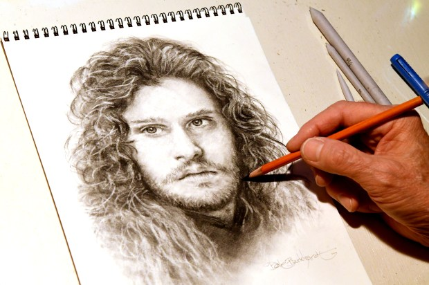 Sketch artist Dale Burkhardt, of Antioch, is photographed with a Sketch of actor Kit Harington as Jon Snow from Game of Thrones in his home studio in Antioch, Calif., on Wednesday, Oct. 25, 2017. Burkhardt, who is retired, has spent his lifetime with a pastime of art. He enjoys mainly sketching sports figures and Hollywood types. Some of his artwork has hung at area restaurants and more. (Doug Duran/Bay Area News Group)