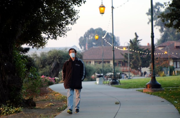 A walker wears a mask as her walks around Lake Merritt in Oakland, Calif., on Thursday, Oct. 12, 2017. Smoke from the Wine Country wildfires have choked the Bay Area closing schools, cancelling flights, and instigating health advisory warnings from the Bay Area Air Quality Management District. (Laura A. Oda/Bay Area News Group)