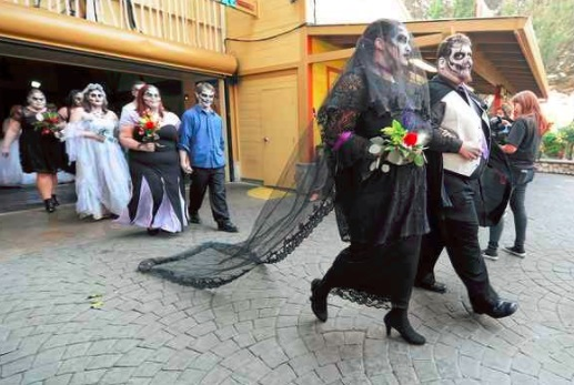 Nubia Gray and Brandon Freeman walk arm-in-arm as they take part en masse zombie themed 'Hallowedding' with 13 other couples on Friday the 13th at Six Flags Discovery Kingdom in Vallejo. (Chris Riley­ — Times-Herald)