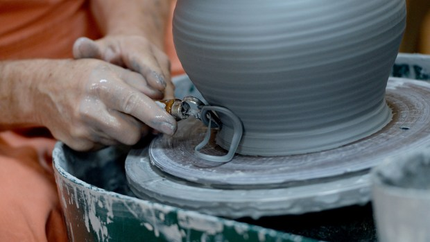 Jerry Illers works on a pot at The Mad Potter in downtown Brentwood, Calif., on Wednesday, Nov. 8, 2017. This new business offers the experience of throwing clay on the pottery wheel, classes in pottery and ceramics and glass fusion as well as hosting parties for groups. (Dan Honda/Bay Area News Group)