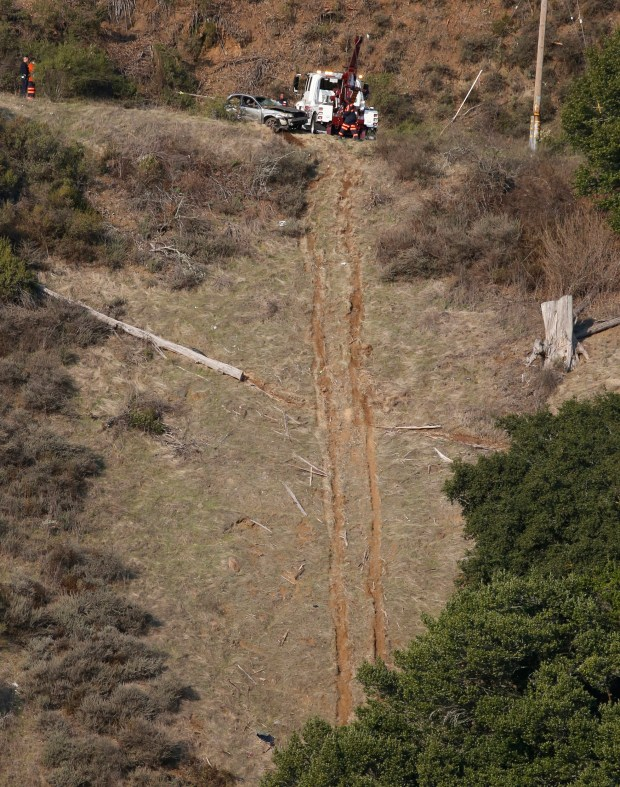 Tow truck workers pull a car up the side of a hill off Grizzley Peak Boulevard after it had careened off the road in Oakland, Calif., on Thursday, Dec. 7, 2017. (Laura A. Oda/Bay Area News Group)