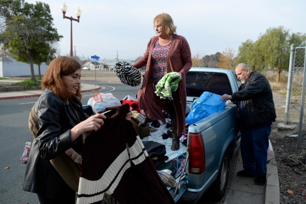 Brenda Schmidt, of Pittsburg, from left, Cynthia Schmidt, of Oakley, and her husband Arnie Schmidt, of Oakley, help sort donated clothes in Antioch, Calif., on Sunday, Dec. 31, 2017. The clothes are provided by The Oakley Foundation, a nonprofit that helps the homeless and families in need founded by Leonard Hernandez. Hernandez started the foundation a year and a half ago and distributes the donated clothes to the homeless every Sunday. (Jose Carlos Fajardo/Bay Area News Group)