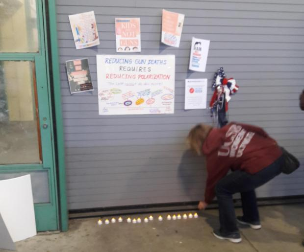 Alameda mother Frances Montell places the 17th candle down at a display honoring the 17 victims of the Parkland, Florida, school shooting. (Laura Casey/For Bay Area News Group)