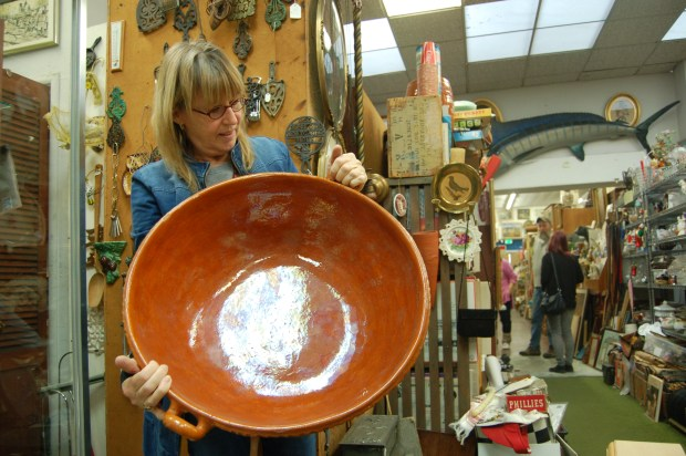 Karen Roach, the daughter of Pauline's Antiques owner Pauline Kelley, inspects a large, clay pot while sorting through items for sale on March 9 in Pauline's Antiques to prepare for a retirement sale that's set to begin this weekend. (Darin Moriki/For Bay Area News Group)