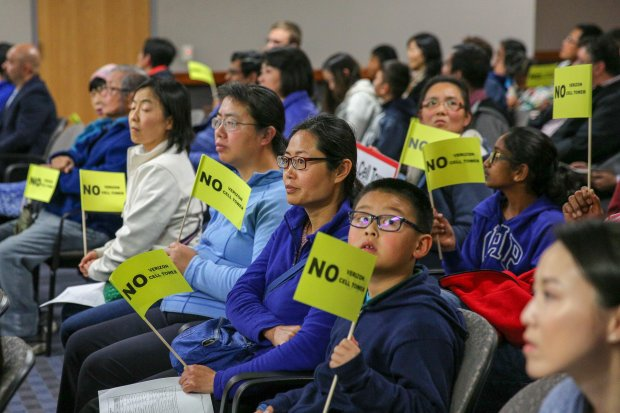 """Many residents at Fremont's City Council meeting on Tuesday, March 13,2018, held signs that read """"No Verizon Cell Tower."""" The Council voted 3-2 at the meeting to overturn a Planning Commission decision that would have allowed the tower to be built. Verizon could sue the city over the decision. (Joseph Geha/Bay Area News Group)"""