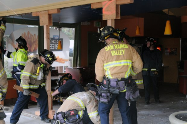 San Ramon Valley firefighters with the department's urban search and rescue unit used tools and materials to shore up the front entrance of a Taco Bell after a car crashed into it Sunday, March 18, 2018.