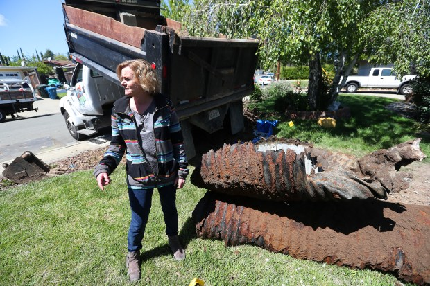 Home owner Kelly O'Connell is photographed next to a segment of corrugated metal storm drain pipe that was removed from her backyard on Tuesday, April 17, 2018, in Pacheco, Calif. The failed pipe caused a sink hole on her property and is being replaced at an expense of $30,000 to her and the neighboring home owner. (Aric Crabb/Bay Area News Group)